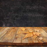 Autumn background of fallen leaves over wooden table and blackboard backgrond with room for text Royalty Free Stock Photo