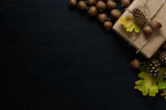 Autumn background with present box, oak leaves, acorns and pines. On black wooden background. Top view stock photo