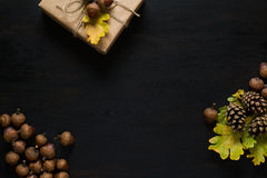 Autumn background with present box, oak leaves, acorns and pines. On black wooden background. Top view royalty free stock images