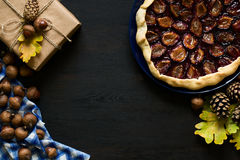 Autumn background with present box, oak leaves, acorns, pines and fruit galette pies. On black wooden background. Top view royalty free stock photos