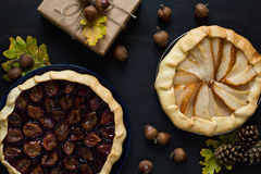 Autumn background with present box, oak leaves, acorns, pines and fruit galette pies Royalty Free Stock Photo