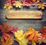Autumn background with signboard, orange leaf on old grunge wood. Deck, copy place for inscription, top view, tablet for text stock photography