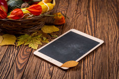 Autumn background and tablet on wooden boards. Space for your text. Selective focus. Stock Photos