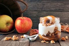Baked apple parfait with caramel in a mason jar on rustic wood Stock Image
