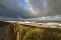 Autumn Beach. Path leading through the dunes to the beach in autumn light and a stormy sky royalty free stock photo