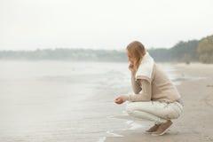 Autumn on the beach. Beautiful girl sitting on the beach Royalty Free Stock Image