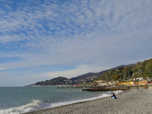Autumn beach, sea coast Sochi, Russia. People relax on the beach at sunny autumn day Royalty Free Stock Photo