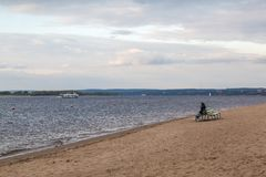 Autumn beach on the Volga. The lonely figure of a woman on the bench. The City Of Samara, Russia Royalty Free Stock Photography