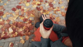 Autumn beautiful maple leaves. Top view of young stylish woman sitting in city park drinking coffee 4k stock video footage