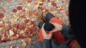 Autumn beautiful maple leaves. Top view of young stylish woman sitting in city park holding a paper cup of coffee 4k stock footage