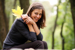 Autumn beauty. Beautiful romantic brunette with golden autumn leaf Stock Photography