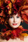 Autumn Beauty. Beautiful Woman with Fall Maple Leaves Wreath. And Fashion Makeup royalty free stock photography