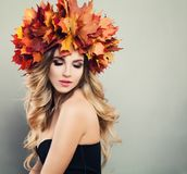 Autumn Beauty. Beautiful Woman Spa Model. With Wavy Blonde Hair, Makeup and Fall Leaves Wreath on Gray Background with Copy space Stock Photos
