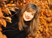 Autumn beauty woman portrait. Horizontal portrait of a beautiful brunet smiling woman surrounded by branches of orange leaves. With blured orange background and stock photography