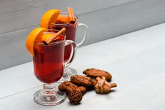 Autumn beverage concept. Glasses with mulled wine or drink near chocolate cookies on white background. Drink or beverage. With cinnamon sticks, orange fruit and Royalty Free Stock Photo