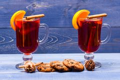 Autumn beverage concept. Glasses with mulled wine or drink near chocolate cookies on wooden background. Drink or. Beverage with cinnamon sticks, orange fruit Royalty Free Stock Photography
