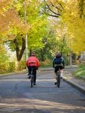 Autumn bicyclists. Warm-up in city park Royalty Free Stock Photography