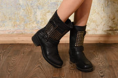 Autumn black women's boots in the straps and rivets Stock Images