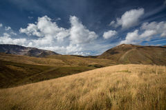 Autumn blue sky with white clouds and mountains on the yellowed Stock Images