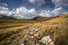 Autumn blue sky with white clouds and mountains on the yellowed Royalty Free Stock Photography