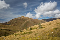 Autumn blue sky with white clouds and mountains on the yellowed Royalty Free Stock Photo