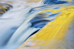Autumn, Bond Falls Cascade. Bond Falls cascade captured with motion blur and illuminated by reflected color from sunlit autumn maples and blue sky overhead royalty free stock image