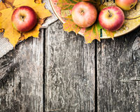 Autumn border from apples and yellow leaves. Autumn border from apples and fallen leaves on old wooden table royalty free stock image
