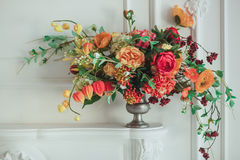 Autumn bouquet on the fireplace. The cozy interior in white tones.  Royalty Free Stock Images