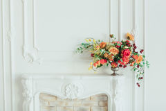 Autumn bouquet on the fireplace. The cozy interior in white tones.  Stock Photos