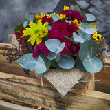 Autumn bouquet of yellow, brown carnations with eucalyptus in a vase wrapped by canvas as decoration street market Stock Images