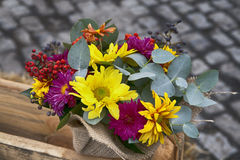 Autumn bouquet of yellow, orange carnations with eucalyptus in a vase wrapped by canvas as decoration street market Stock Image