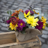 Autumn bouquet of yellow, orange, carnations with eucalyptus in a vase wrapped by canvas as decoration street market Royalty Free Stock Images