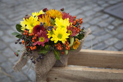 Autumn bouquet of yellow, orange, carnations with eucalyptus in a vase wrapped by canvas as decoration street market Royalty Free Stock Photography