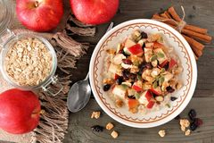 Autumn breakfast oatmeal, overhead scene on rustic wood. Autumn breakfast oatmeal with apples, cranberries, seed and nuts, overhead table scene on rustic wood Stock Photos