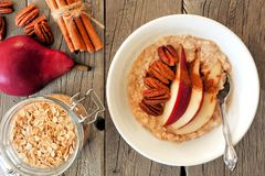 Autumn breakfast scene, oatmeal with red pear, pecans and cinnamon. Autumn breakfast oatmeal with red pear, pecans and cinnamon, overhead scene on rustic wood Royalty Free Stock Images