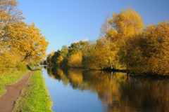 Autumn: Bridgewater canal perspective with water reflections. Bright, colorful fall view with yellow and orange trees reflected in still water. Taken at the Royalty Free Stock Photography