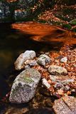 Autumn waterfalls. Autumn brook with stones and leaves Stock Photos