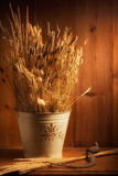 Autumn. Bucket with spikes, straw and dried flowers on a wooden table with a sickle Stock Photo