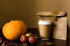 Autumn business lunch, still life with pumpkin, apple and foliage. Paper bag, autumn leaves and hot steaming cup of coffee. Business lunch concept Stock Images