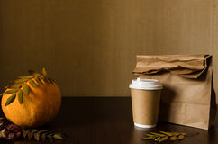 Autumn business lunch, still life with pumpkin and foliage. Dark brown textured background with copy space Stock Photography