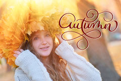 Autumn calligraphy lettering text. Happy young woman with a wreath of yellow leaves walking in the park.  stock photos