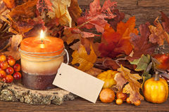 Autumn candle. Over wooden background