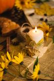 Autumn candle with maple leaves. Vintage paper, yellow flowers, pumpkin royalty free stock photo