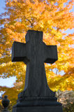 Autumn cemetary cross. A close up of a cross on a cemetary monument at autumn Stock Images