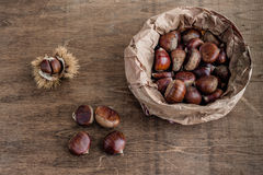 Autumn chestnuts. Chestnuts in a paper bag on a row wooden table with loose nuts and a chestnut husk Royalty Free Stock Photos