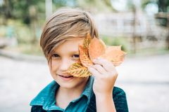 Autumn child boy with autumnal mood. Boy on a breeze in an autumn village. Advertisement concept. Autumn child boy with autumnal mood. Boy on a breeze in an stock photography