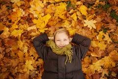 Autumn Child Boy nas folhas de bordo da queda fora foto de stock