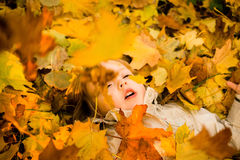 Autumn - child in fallen leaves Royalty Free Stock Photo