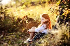 Autumn child portrait. Autumn portrait of a red haired little girl sitting under a tree Stock Photography