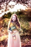 Autumn child portrait. Little girl with long red hair and large blue eyes. Autumn look: brown hat, colorful scarf. Bright sun light in background Stock Photos